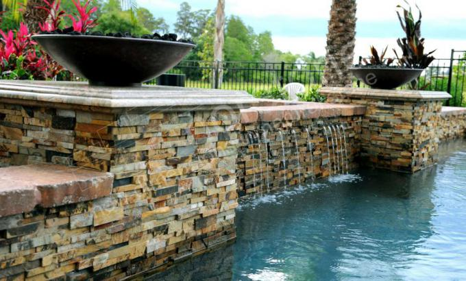 Stacked Stone on a raised beam in a pool with two fire bowls and a waterfall