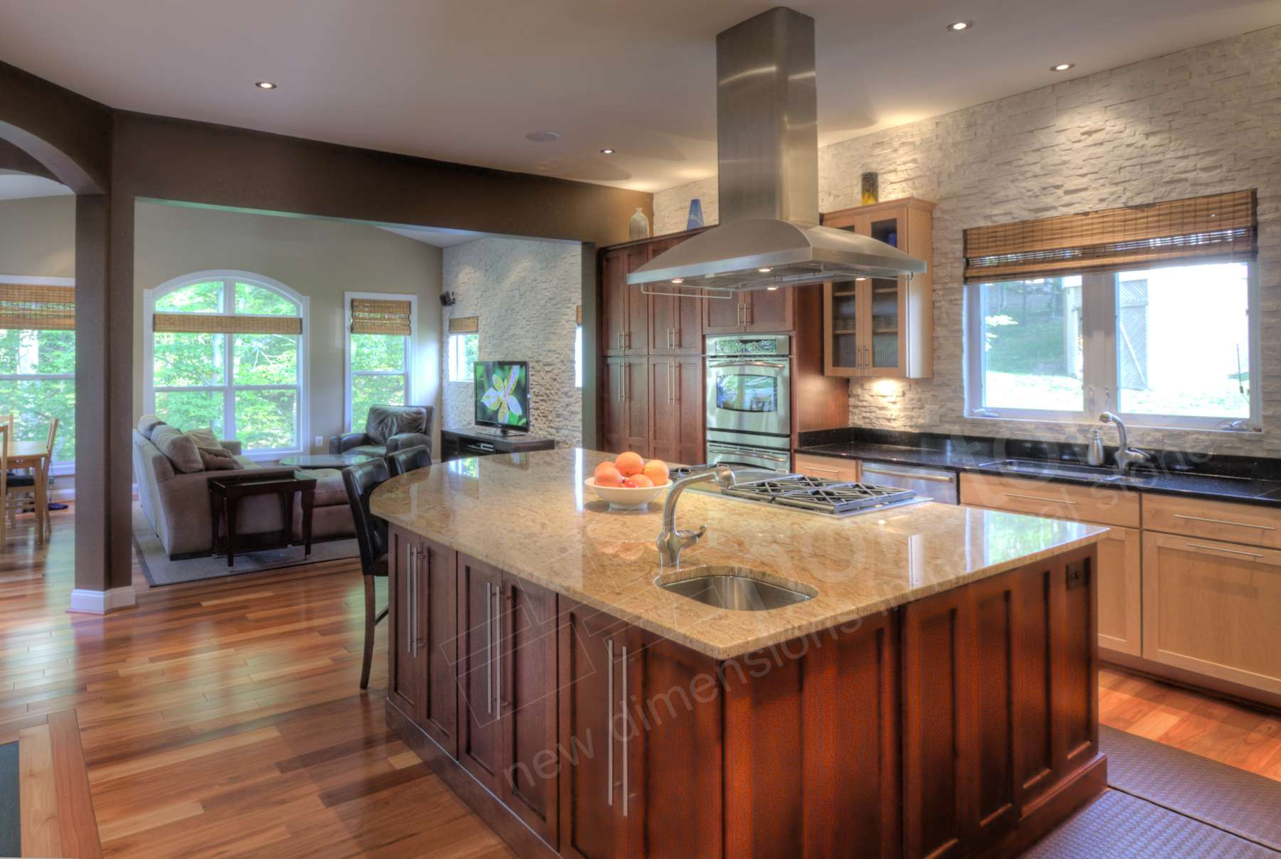 Countertop to ceiling white stacked stone backsplash in a remodeled kitchen with large island