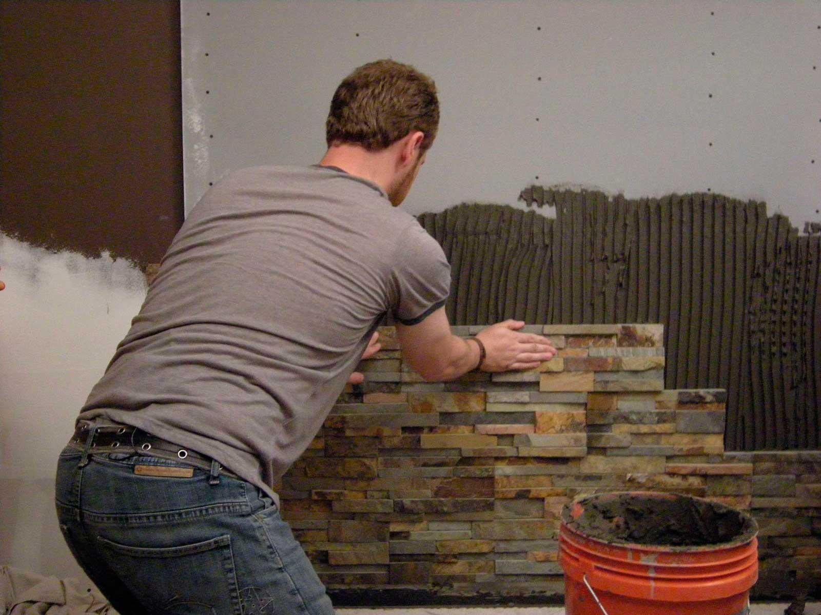 An installer setting stone veneer in a bathroom feature wall