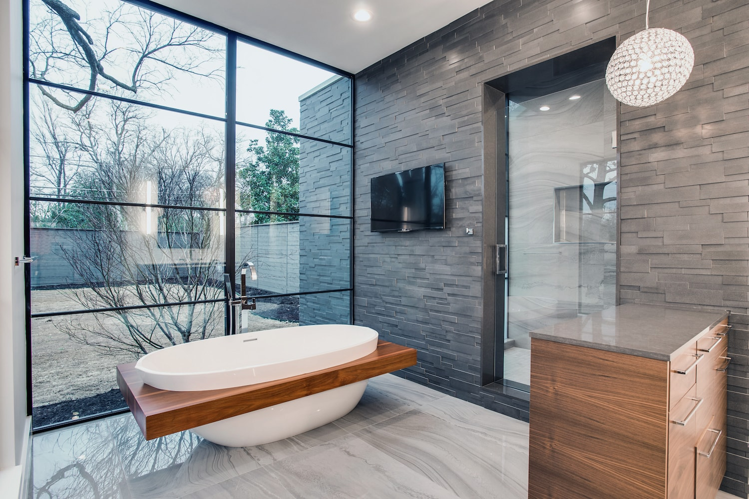 Modern luxury bathroom featuring complimentary light grey polished marble flooring and grey honed stone veneer wall.