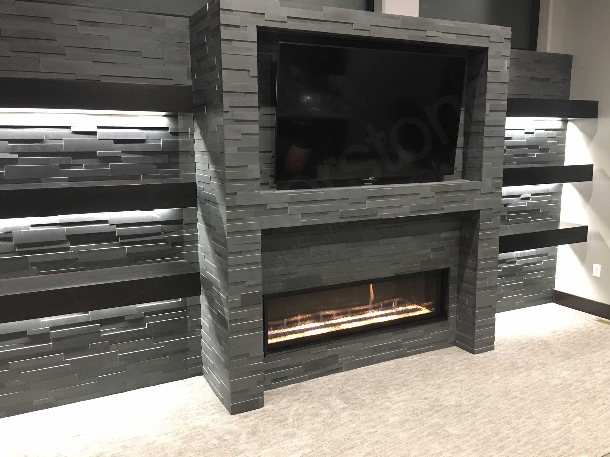 Gas fireplace and big screen tv recessed into a stone wall clad in grey basalt 3D ledge stone flanked on either side by floating shelves