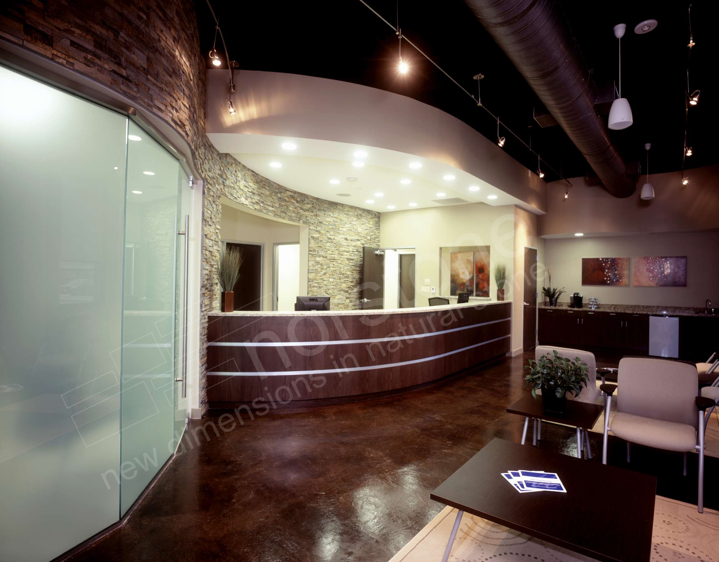 Curved wall starting behind a reception desk and continuing over a large glass doorway in a modern industrial styled medical office.