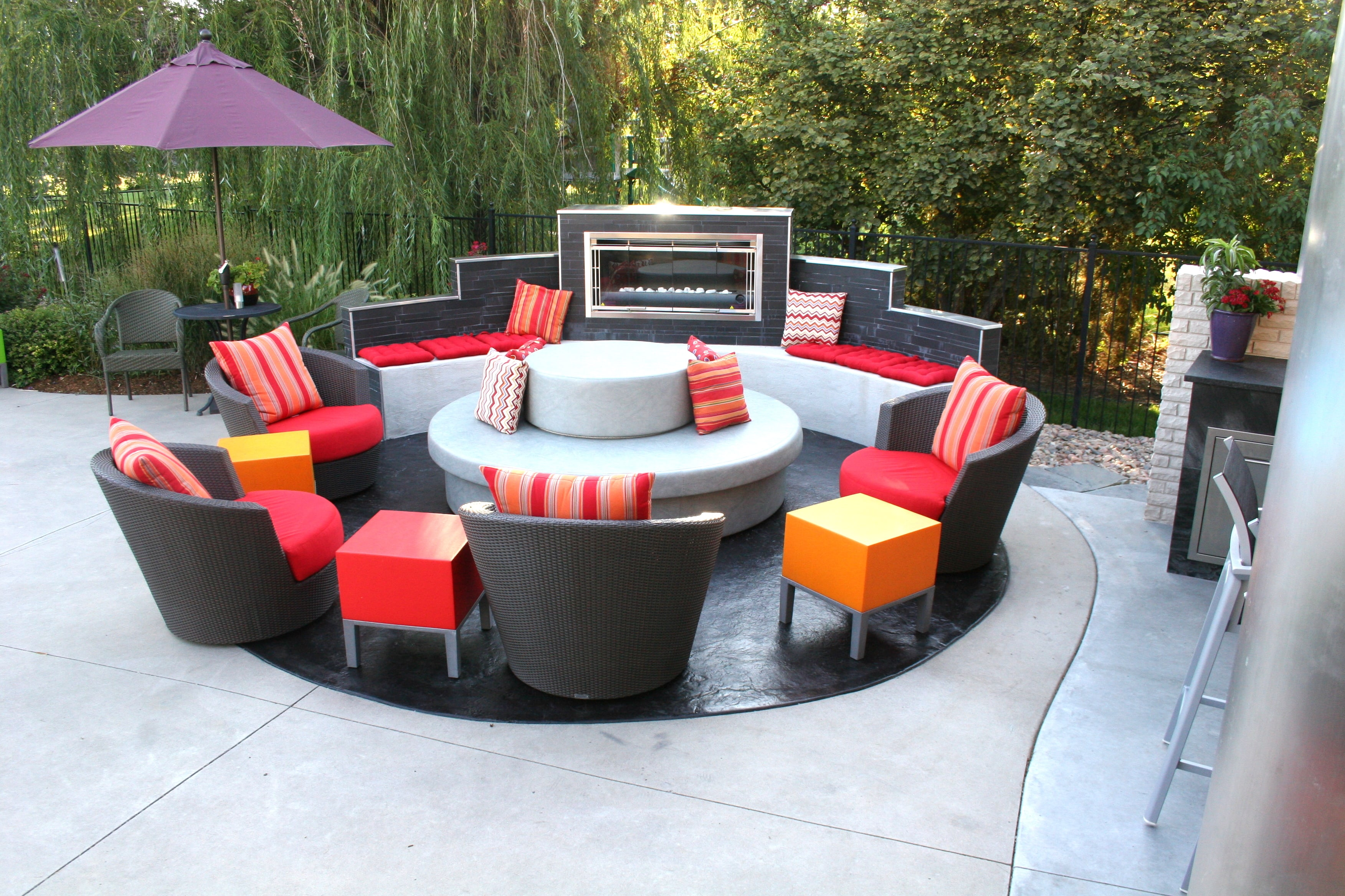Tri level outdoor fireplace partially surrounding a circular conversation area.