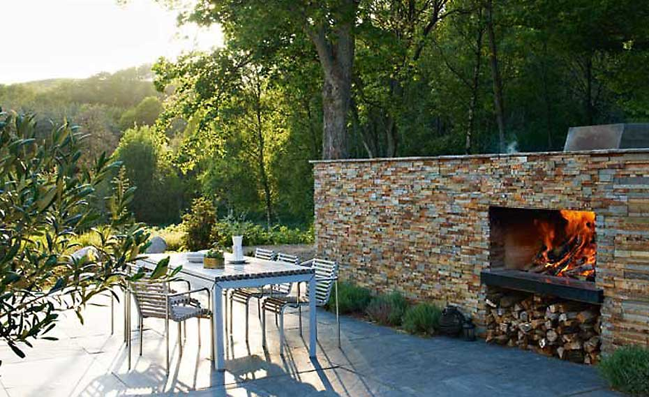 Outdoor wood burning stacked stone fireplace with large firebox