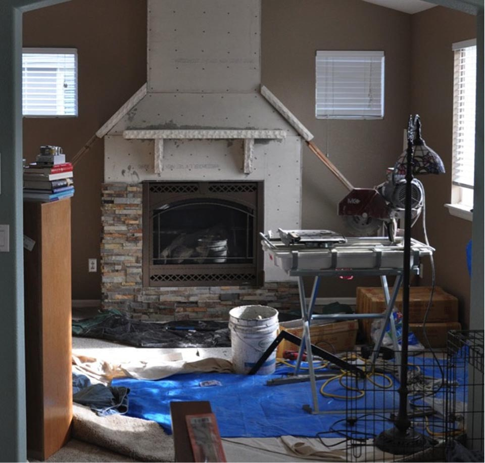 In process installation of stacked stone on a fireplace where a tile wet saw is being used to make the cuts