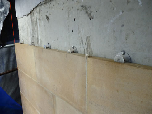 Large limestone veneer slabs directly attached to a concrete substrate using mechanical fasteners
