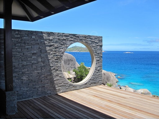 Norstone Charcoal Rock Panels on a Feature Wall in the Seychelles with a circular cut out showing granite formations and another Island in the distance