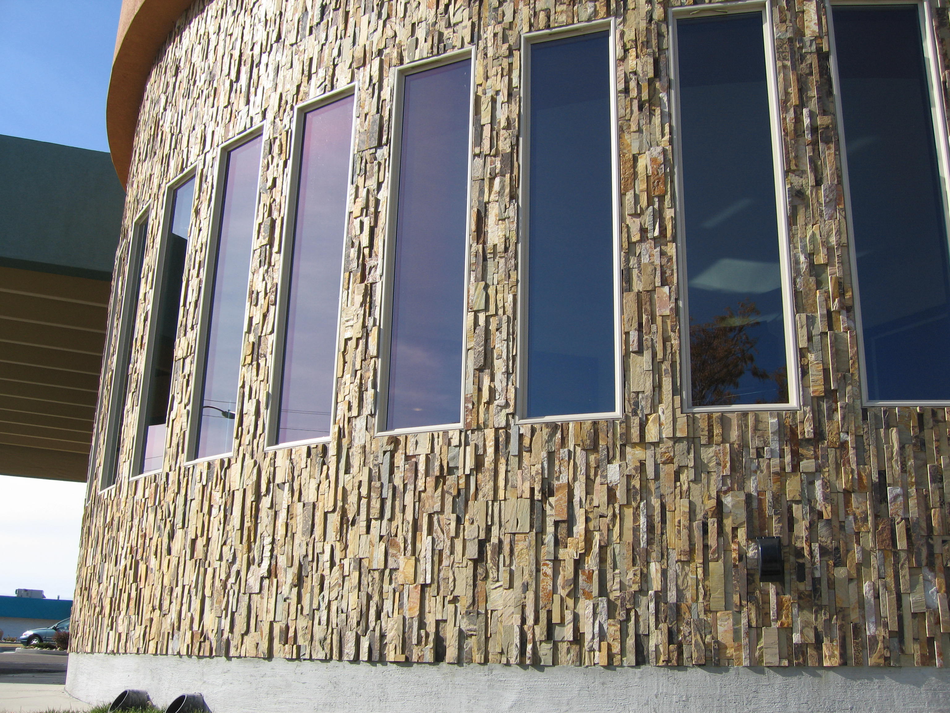 Norstone Ochre Blend Rock Panels installed on a vertical orientation on an exterior convex radius wall
