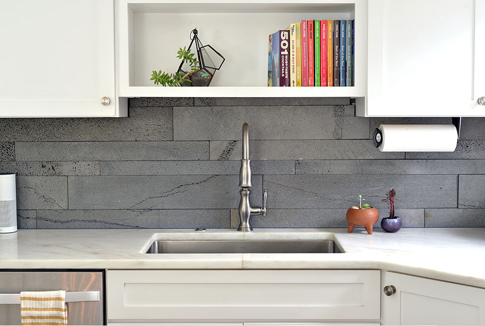 Norstone PLANC large format tile in Platinum color used the backsplash of a modern kitchen with white countertops and white cabinets.