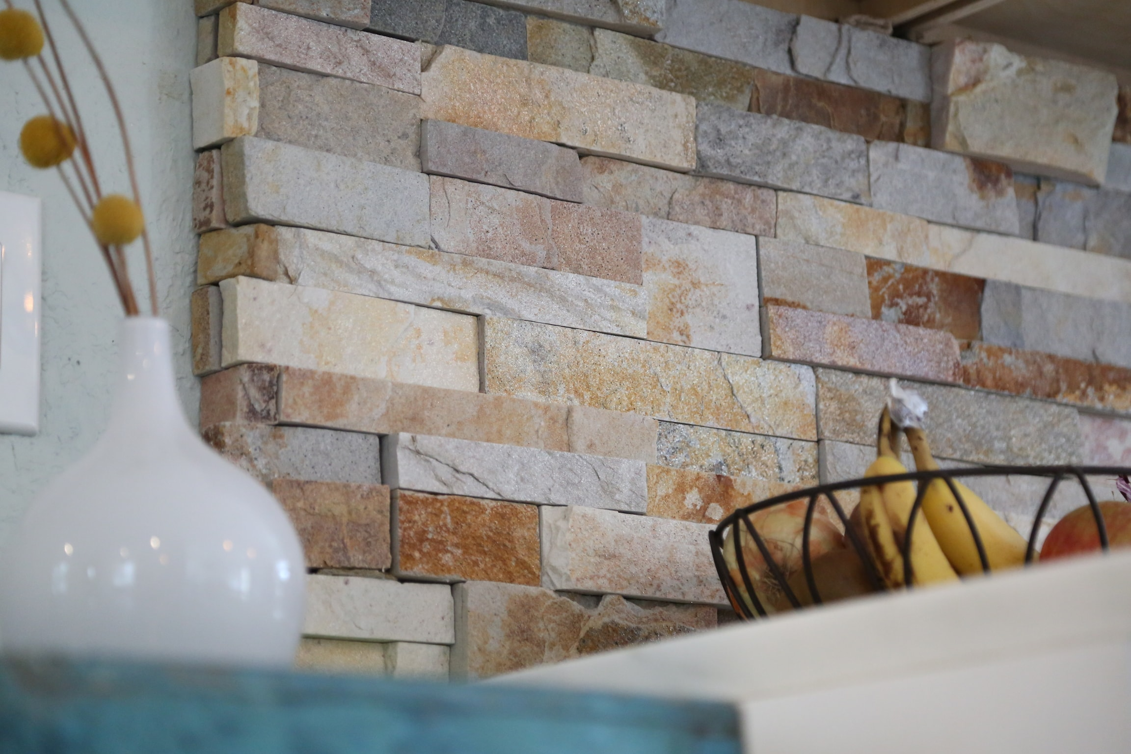 Light colored split face stone veneer used on a kitchen backsplash