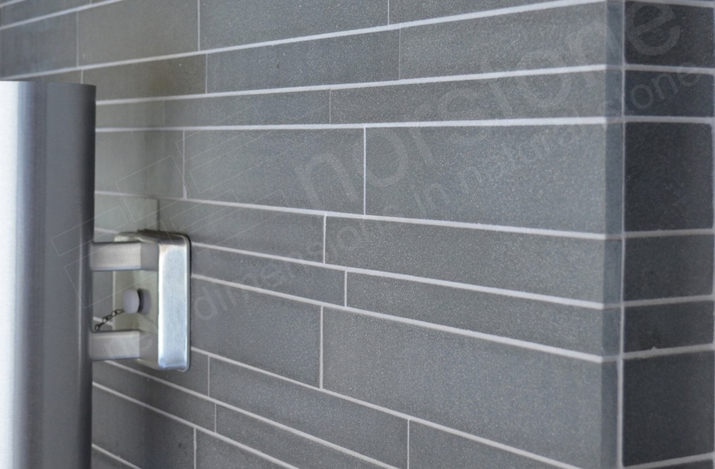 Lava Stone Basalt Interlocking medium format tile used on a wall showing an outside corner and a stainless steel light fixture