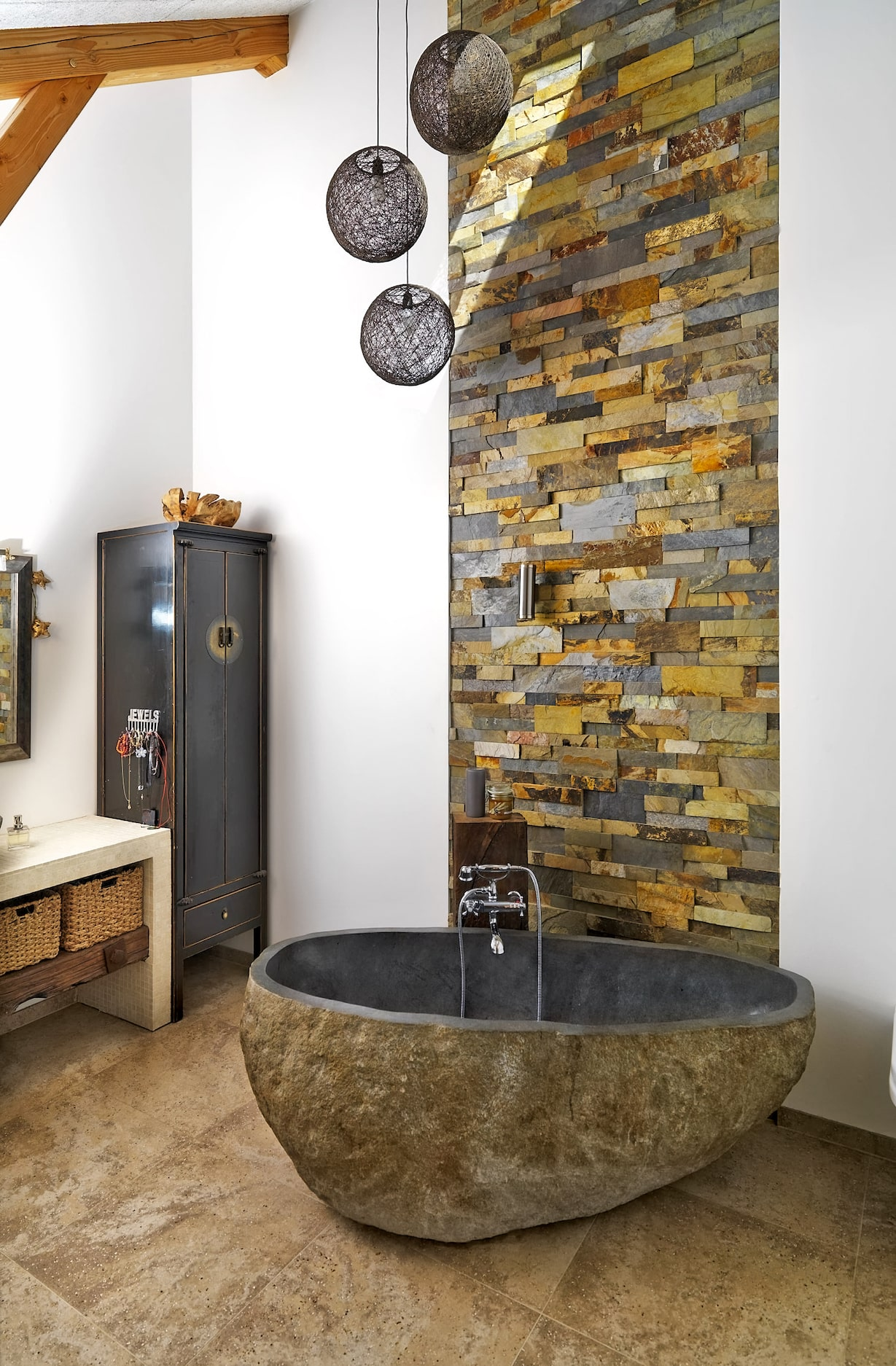 A super unique stone bathroom featuring a floor to ceiling stacked stone feature wall and a freestanding one piece natural stone tub.