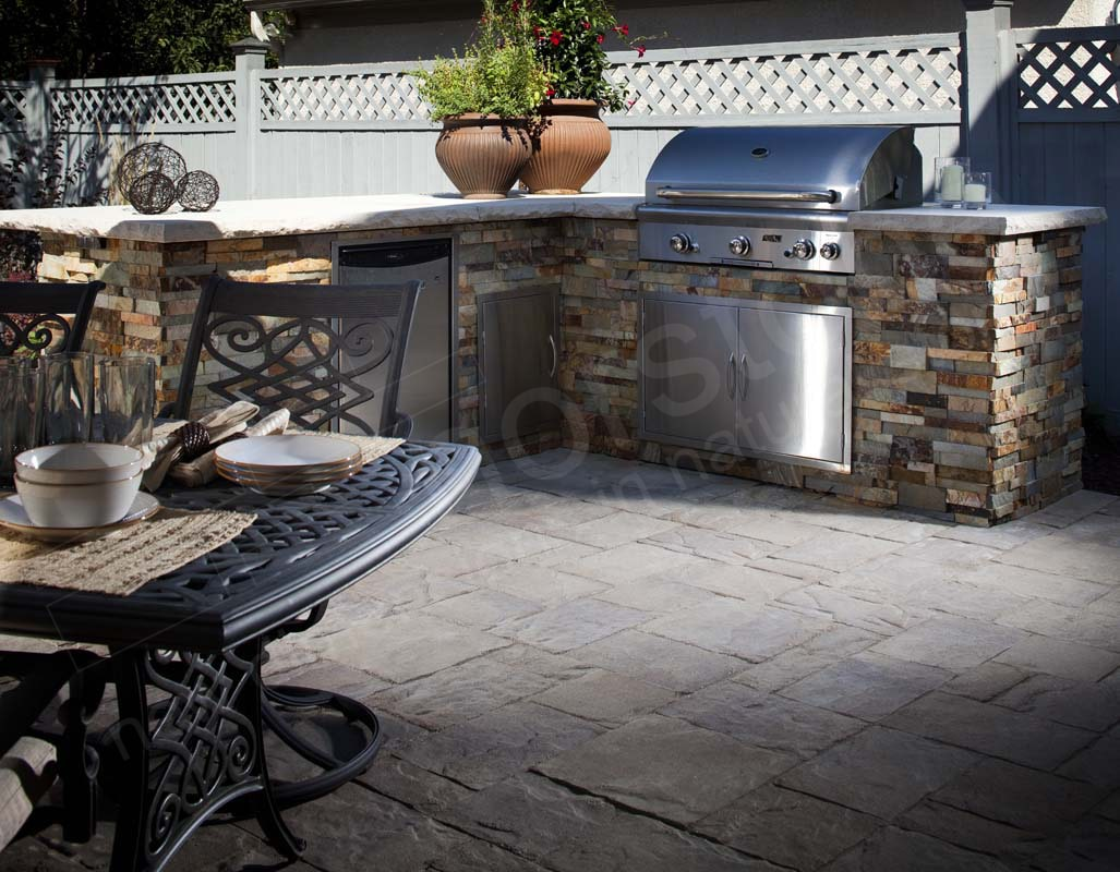 Prefab outdoor grill island and summer kitchen with a metal substrate that has been clad with a stone veneer