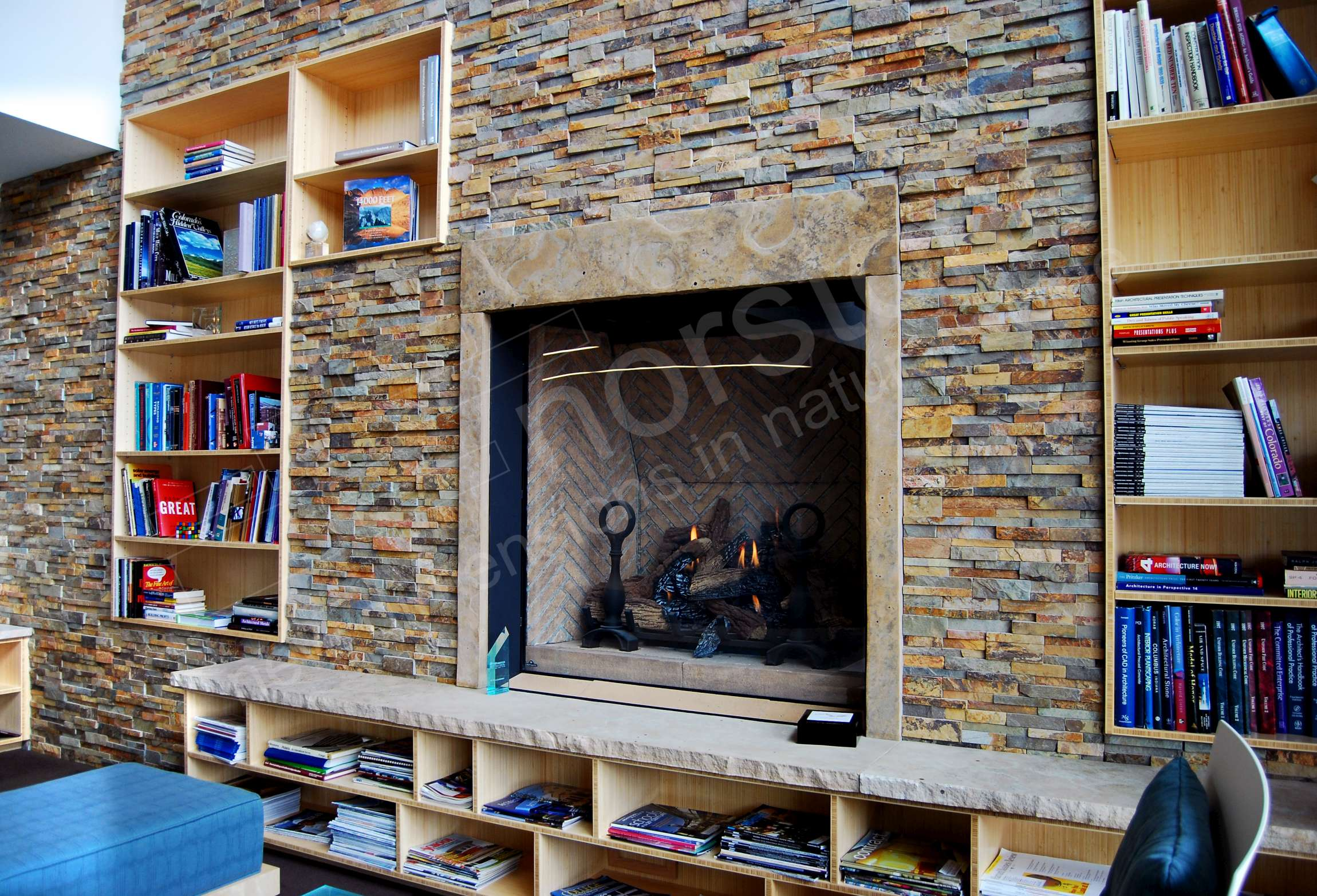Natural Stone Veneer Fireplace with raised cut stone hearth with storage cubbies underneath it.