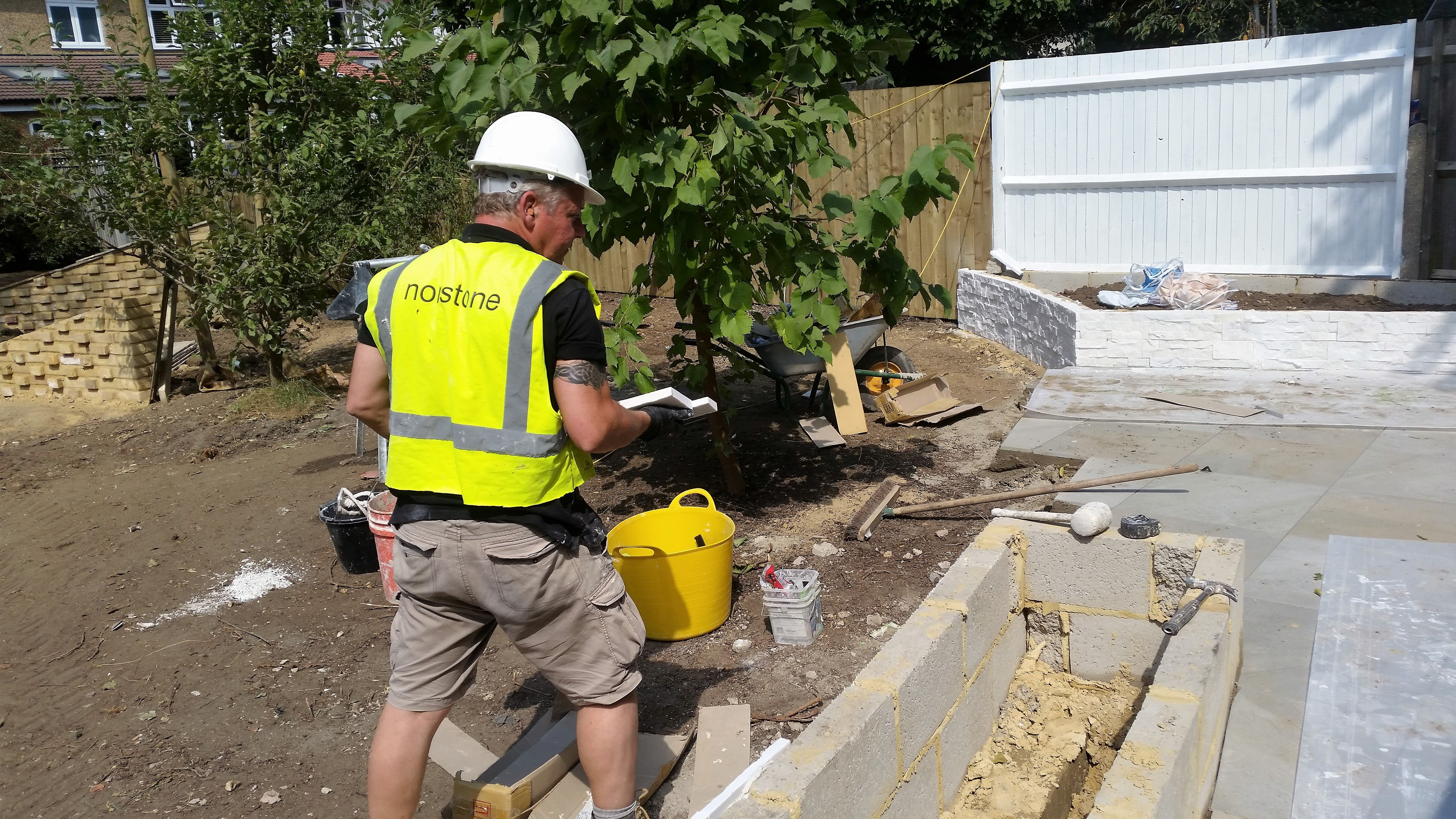 Norstone White Rock Panels being installed on an exterior garden wall and cleaned up post installation without the need for acid.