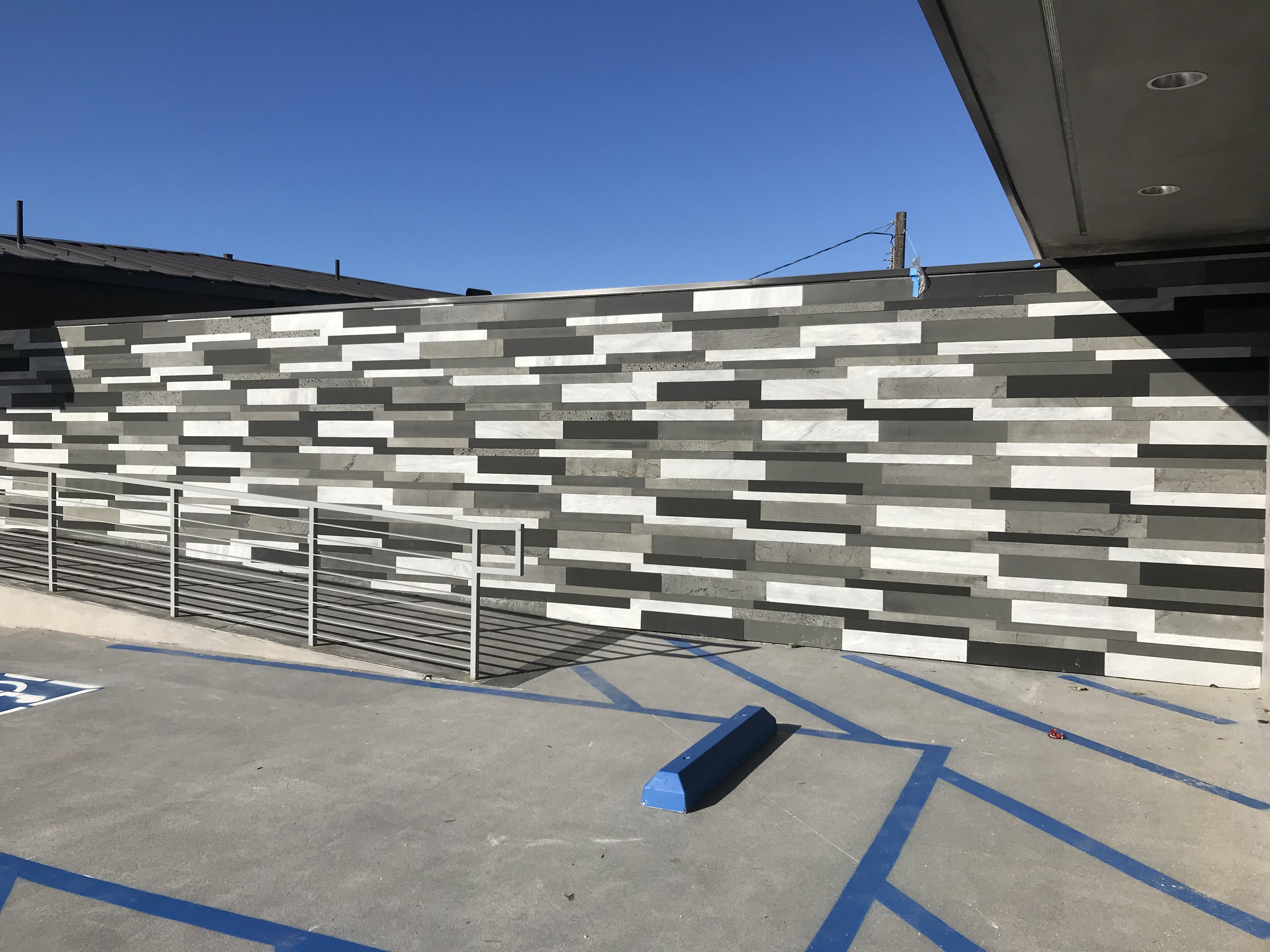 Exterior commercial wall clad in a mix of four colors of Norstone's Large Format Planc Tiles