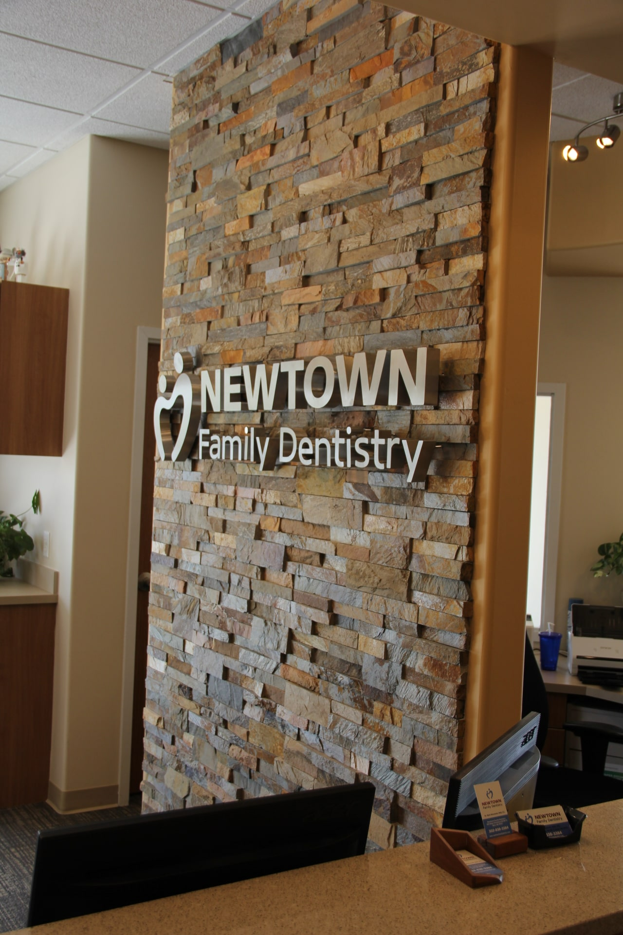 Two Sided Stacked Stone Feature Wall in Dentist Office with Stainless Steel Signage