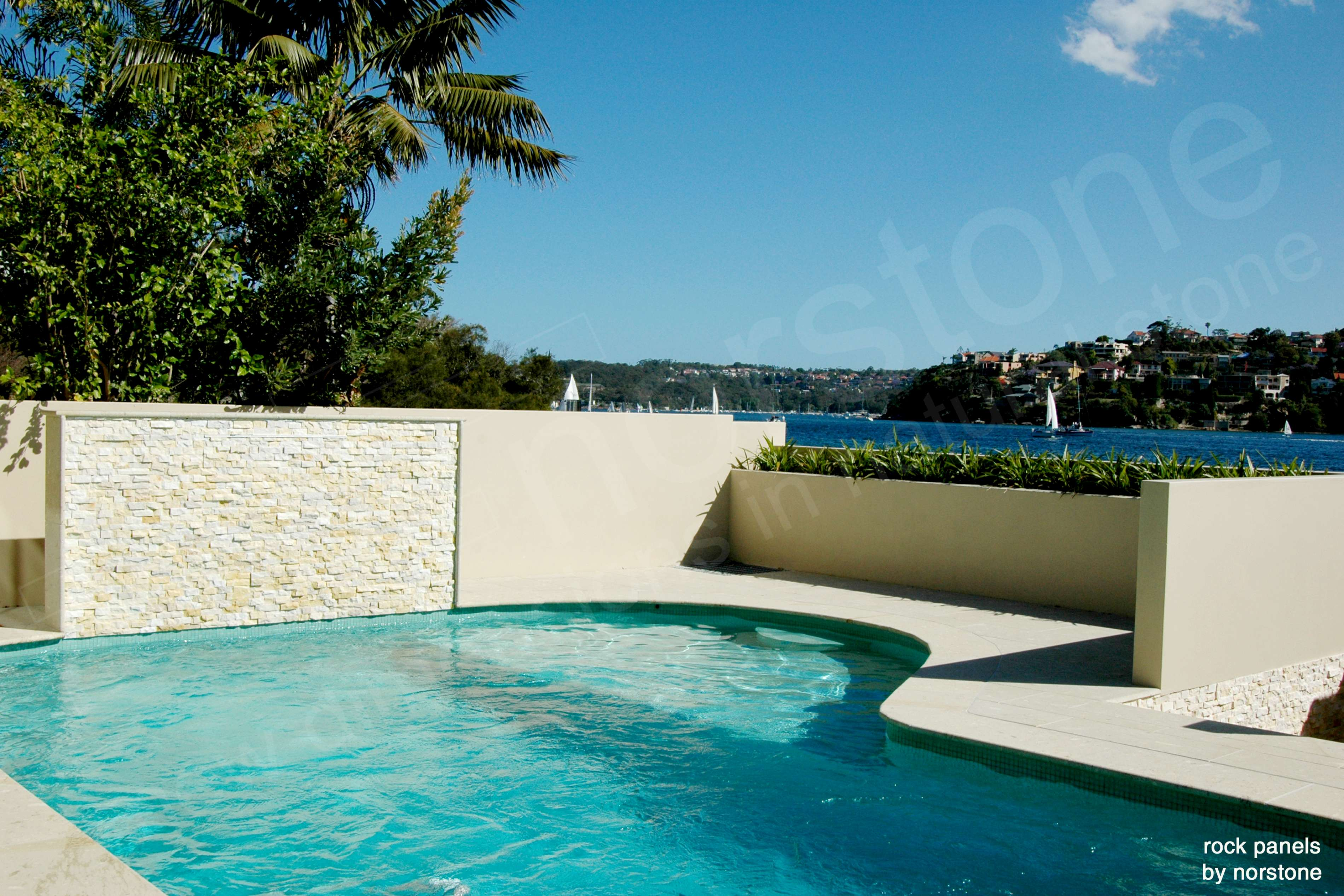 Home on the Coast of Australia featuring Norstone Ivory Rock Panels on a pool feature wall and sea wall