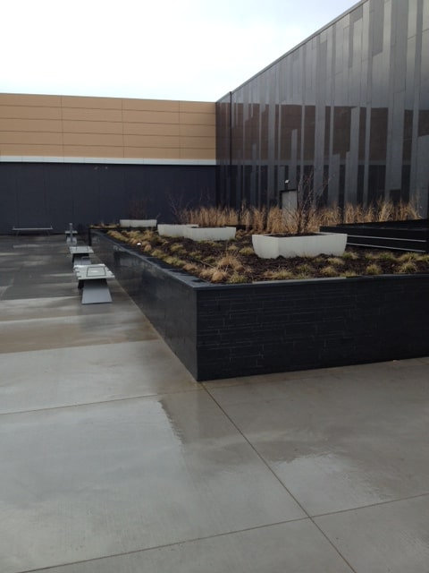 Norstone Lynia Interlocking Tiles in Ebony Basalt color used to clad a commercial landscaping wall as part of a large retail project.
