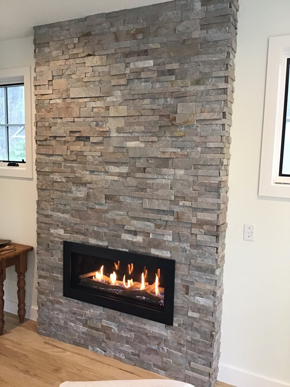 Stacked Stone fireplace clad floor to ceiling in Norstone Sierra XLX Silver Grey color