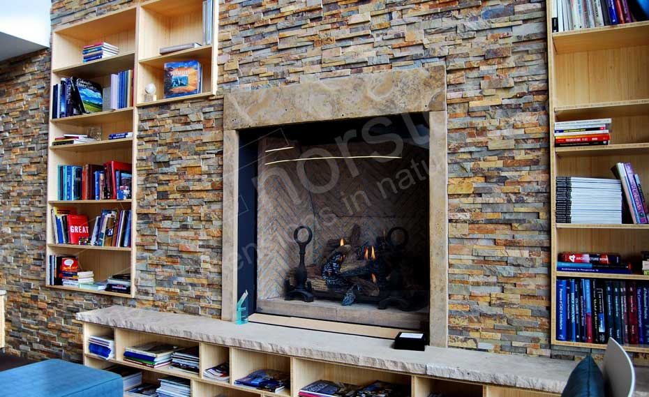 Close-up of a Stone Fireplace Wall with built in wood bookshelves in an architect lobby in Denver