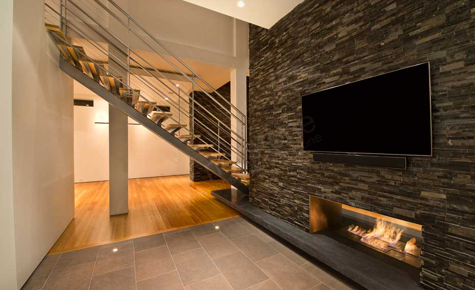Natural Stacked Stone Veneer Wall Cladding on Interior Wall with TV and a fireplace