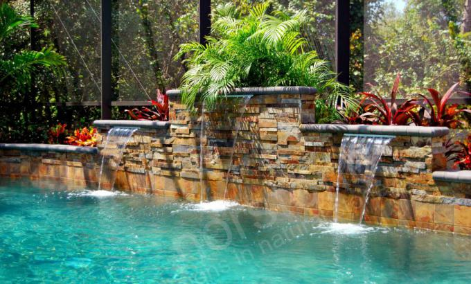 Thin Stone Veneer used under cascading water fall on rising back wall of a pool in Orlando Florida