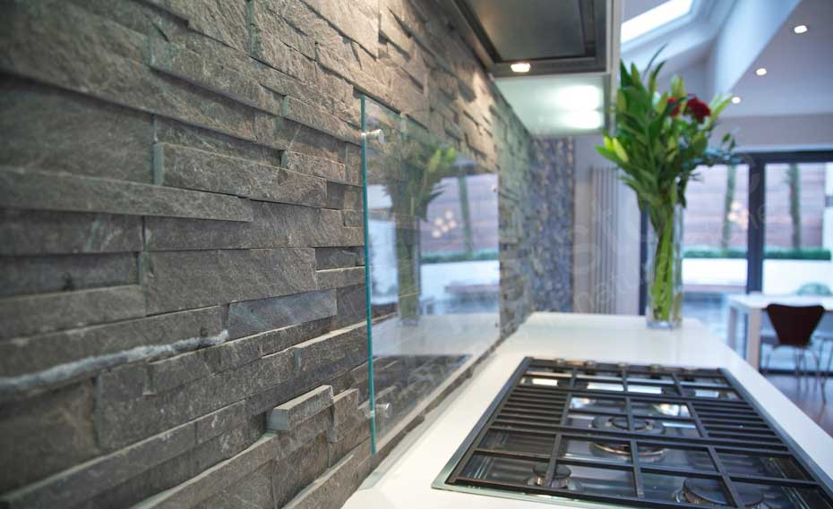Natural Stacked Stone Backsplash made with Norstone series Charcoal Ledgestone panel system with frosted glass guard near stove tops