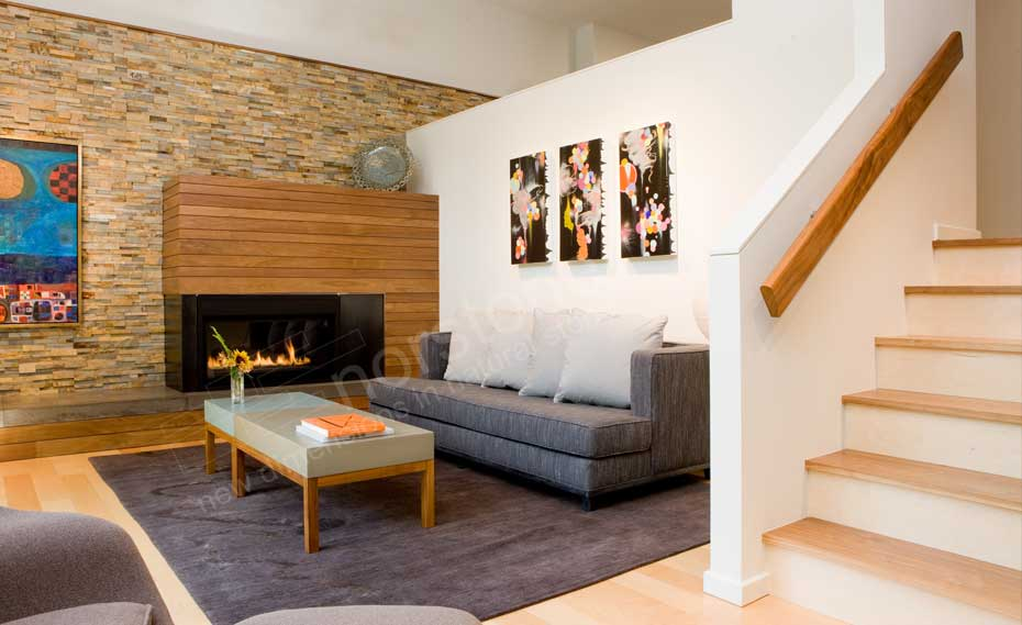 Stacked Stone Fireplace in a living room with a dimensional stone panels used as the feature wall and wood paneling on the fireplace surround