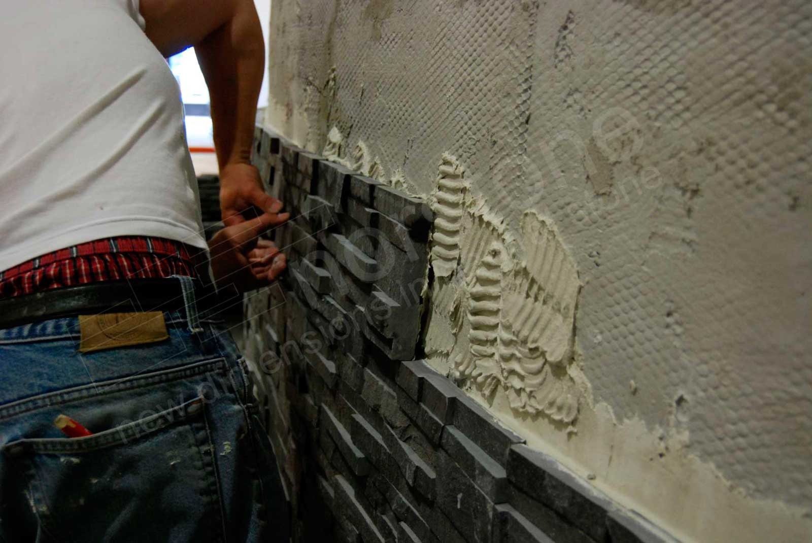 Massachusetts Closeup Of Man Setting A Norstone Stone Veneer Panel In Place On Cement Board Using Modified