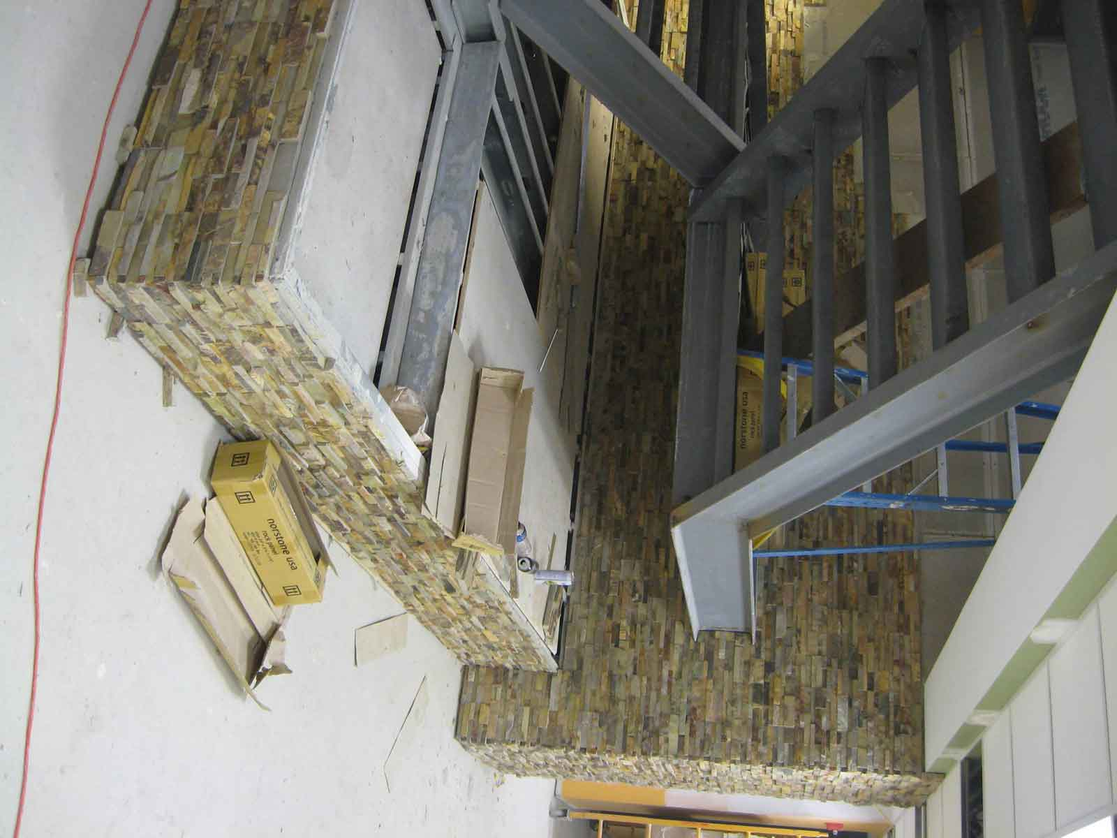 Progress Installation Shot of Norstone Ochre Rock Panels being installed on stairwell at healtchare facility in town of Boston Massachusetts