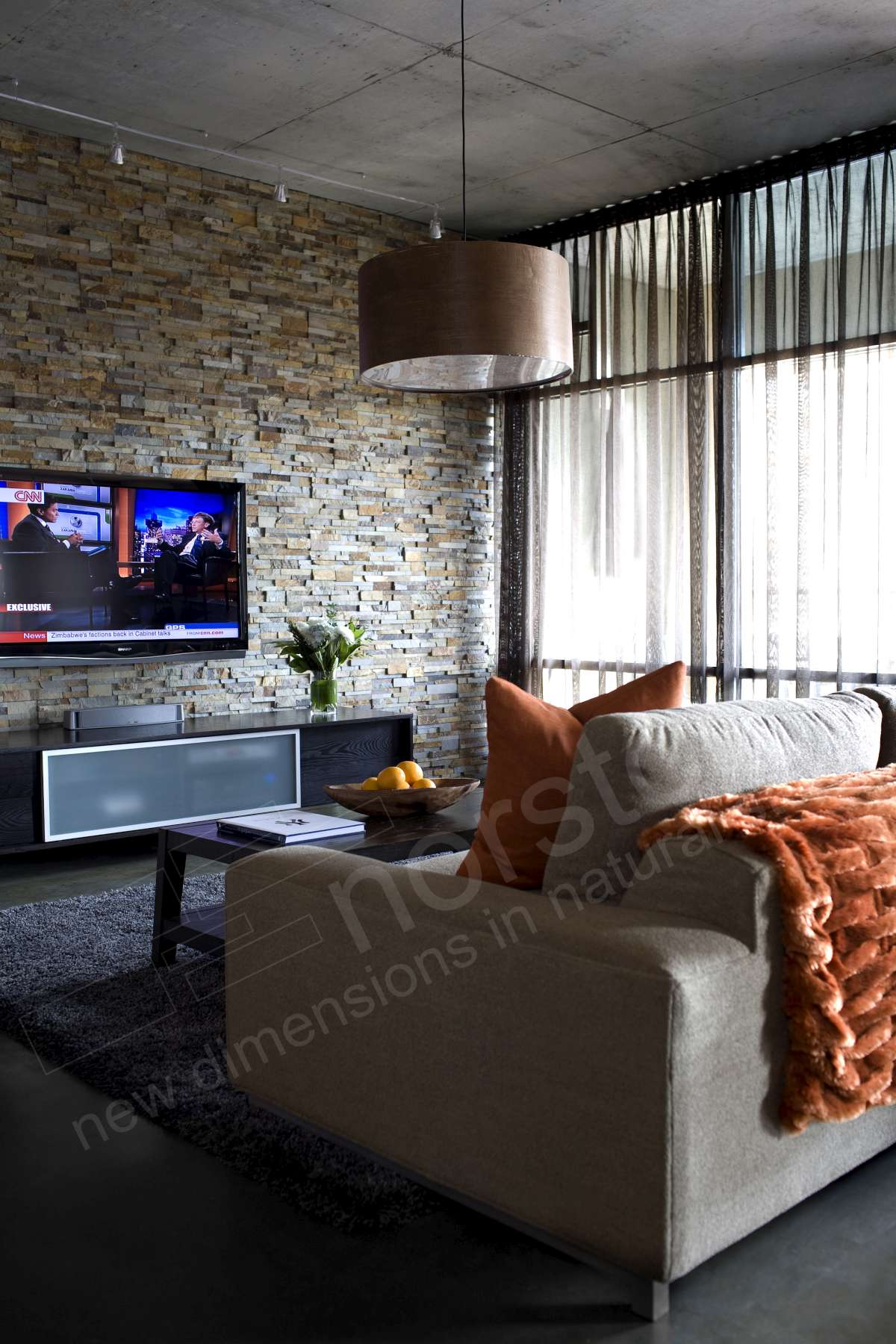 Flat Screen TV installed on Stacked Stone Wall - Living Room