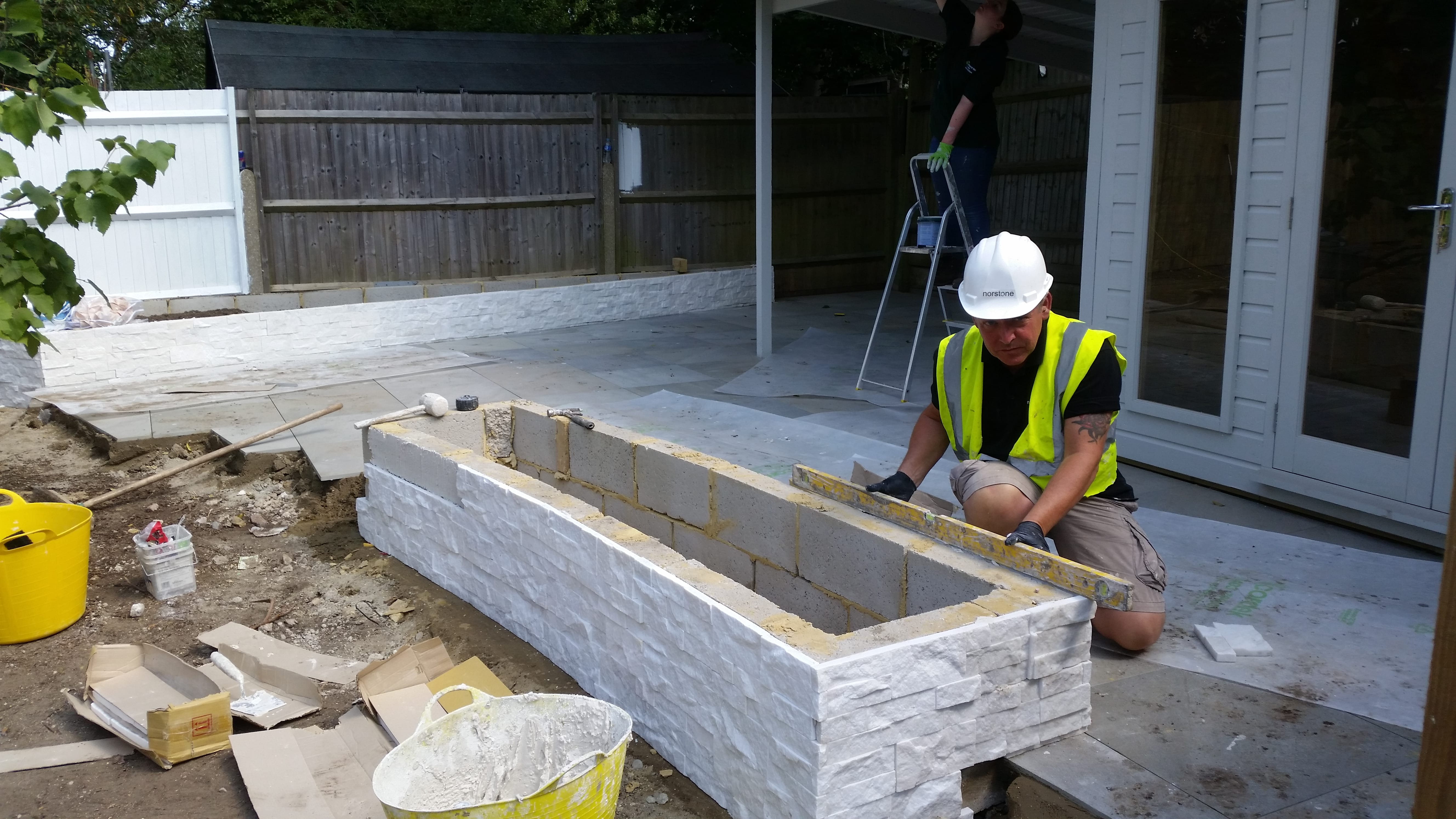 White Stacked Stone being installed on a curved planter box