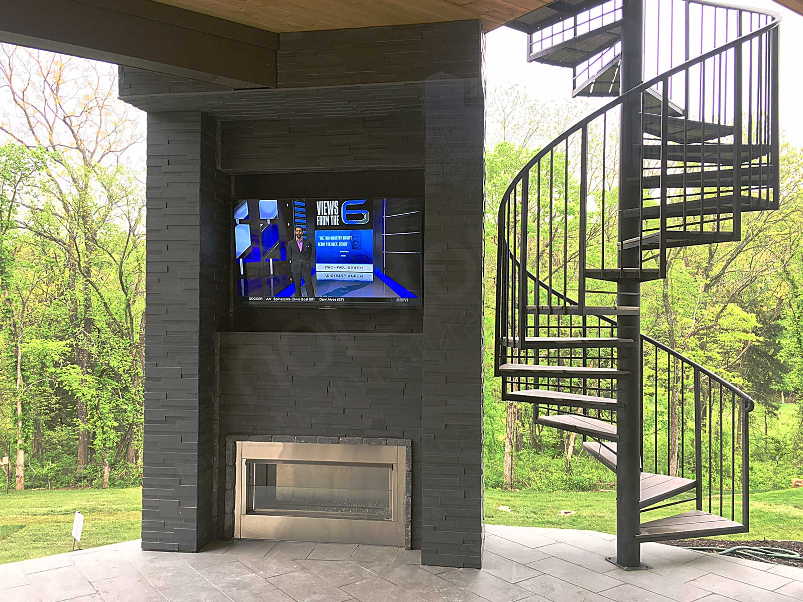 Outdoor fireplace and tv recessed into column clad in basalt 3d ledge stone