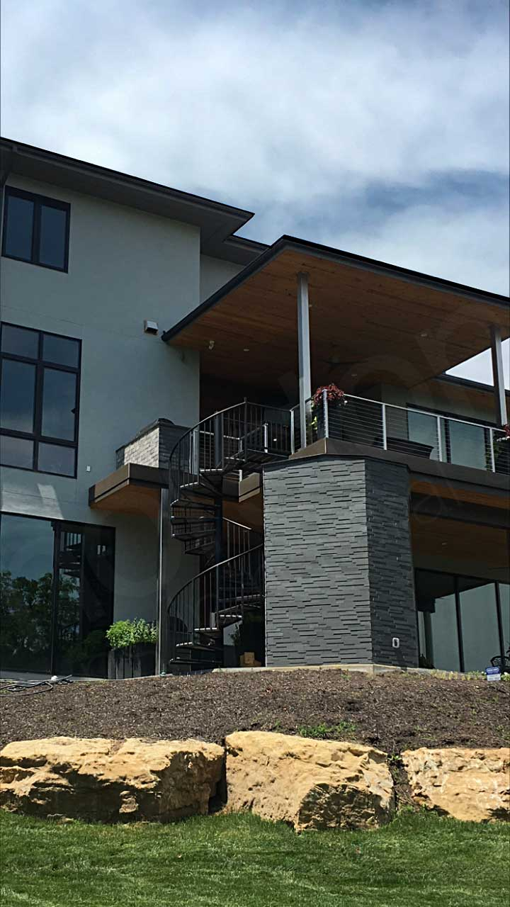 Rear elevation view of modern styled home outside of Kansas with grey basalt 3d ledge stone accents