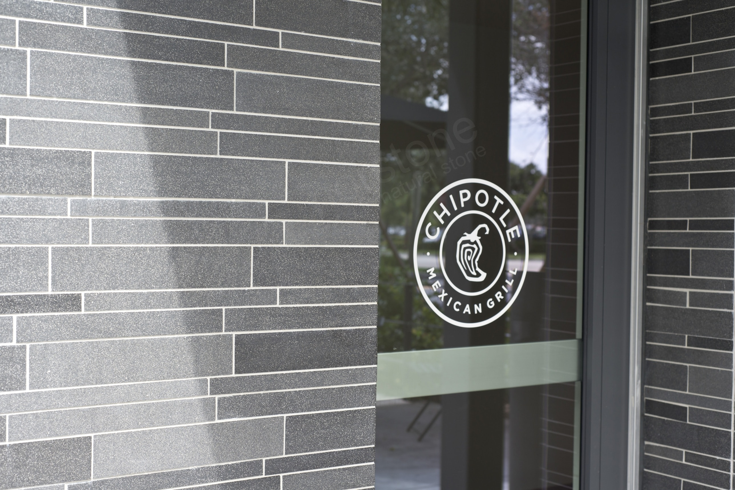 Basalt Mosaic Interlocking Tile with White Grout complementing Chipotle Logo