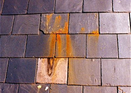Slate roofing tiles that have not been sealed and are rusting due to high iron content