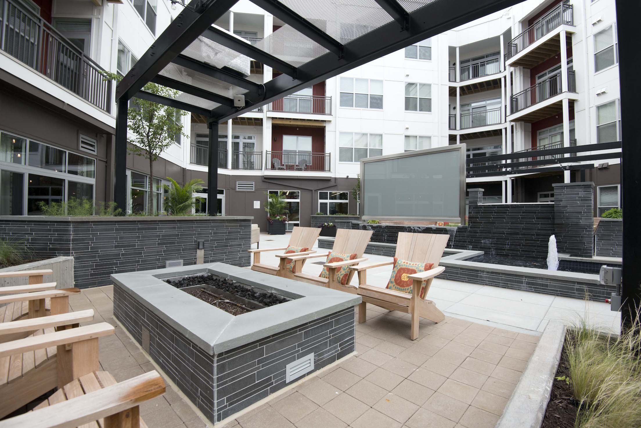 Apartment common area gas firepit with basalt stone tile used as the veneer