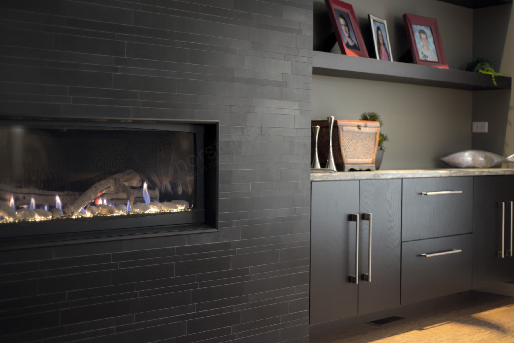 Modern All Glass Fireplace Insert set at waist level on a black stone tile fireplace