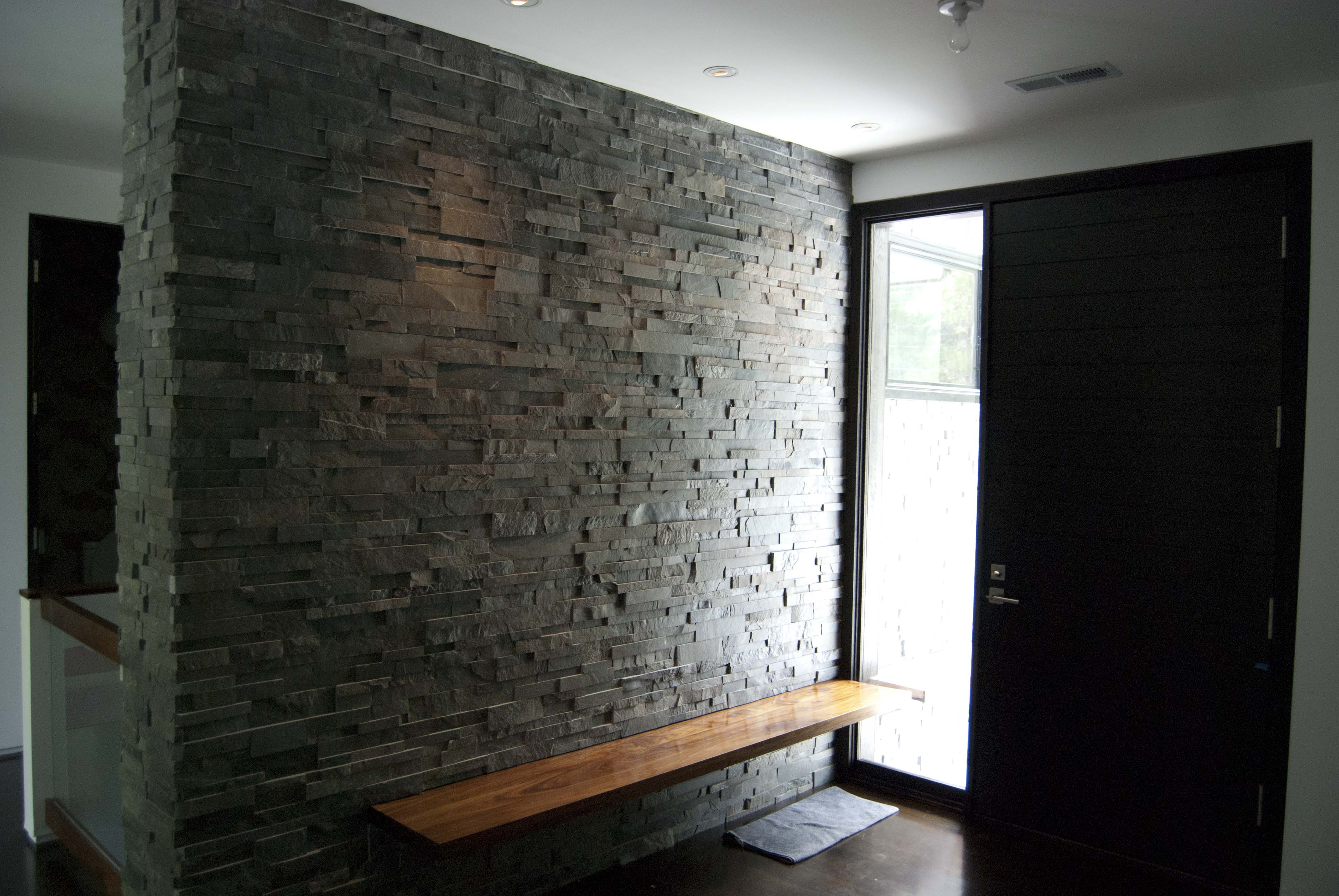Charcoal Colored Stone Accent Wall in entryway of home with floating bench
