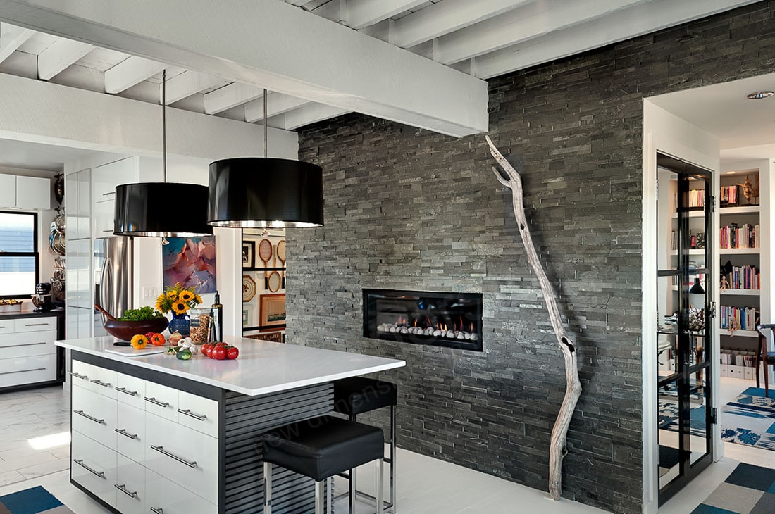 Charcoal Stone Veneer Wall in Kitchen with a ventless gas fireplace and tree branch art