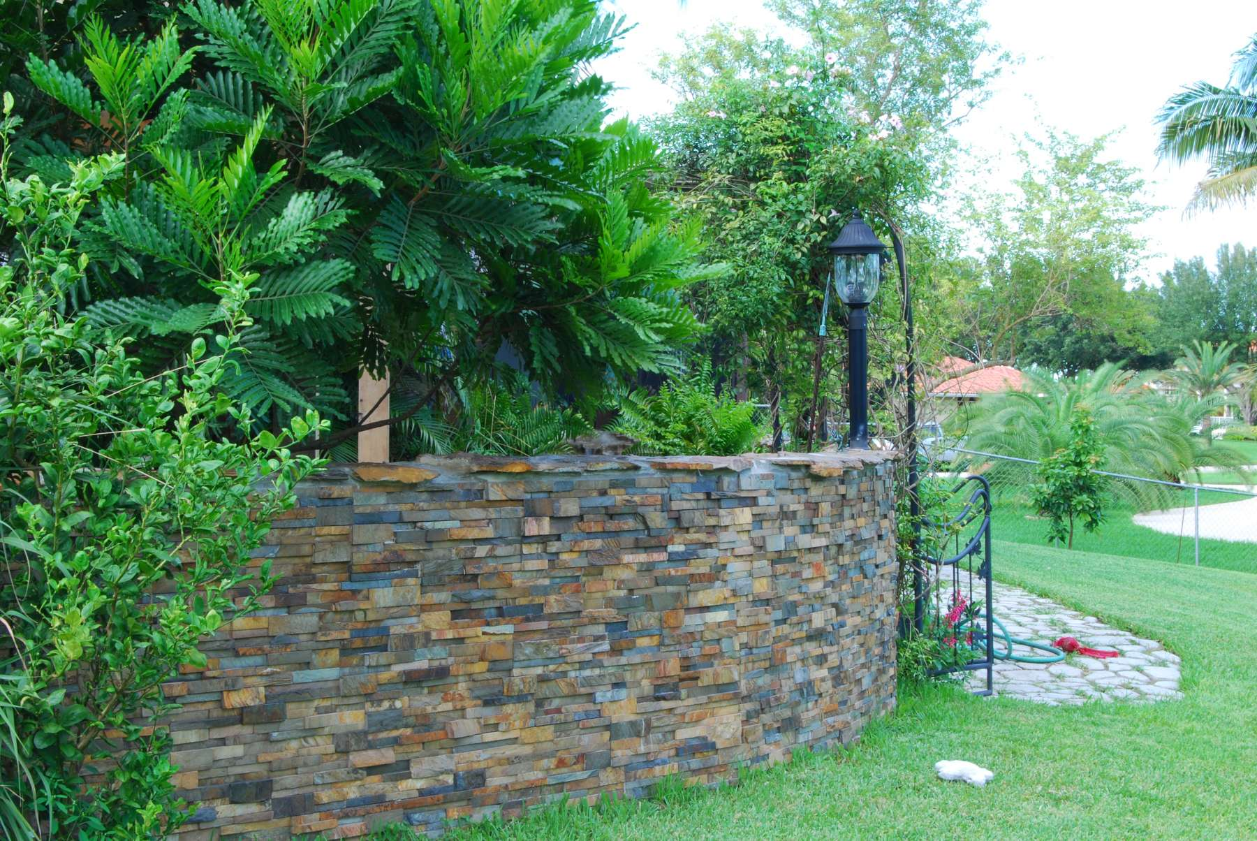 Curved Stacked Stone garden wall that has been sealed with an enhancing sealer