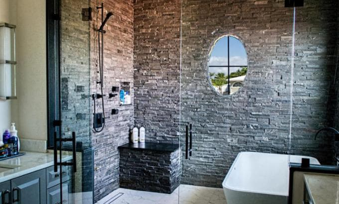 Large Walk In Shower with a Frameless Glass Enclosure and Stacked Stone used on the walls