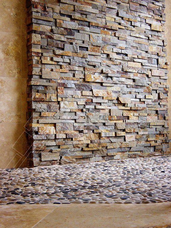 Stacked Stone on a shower wall with a pebble floor