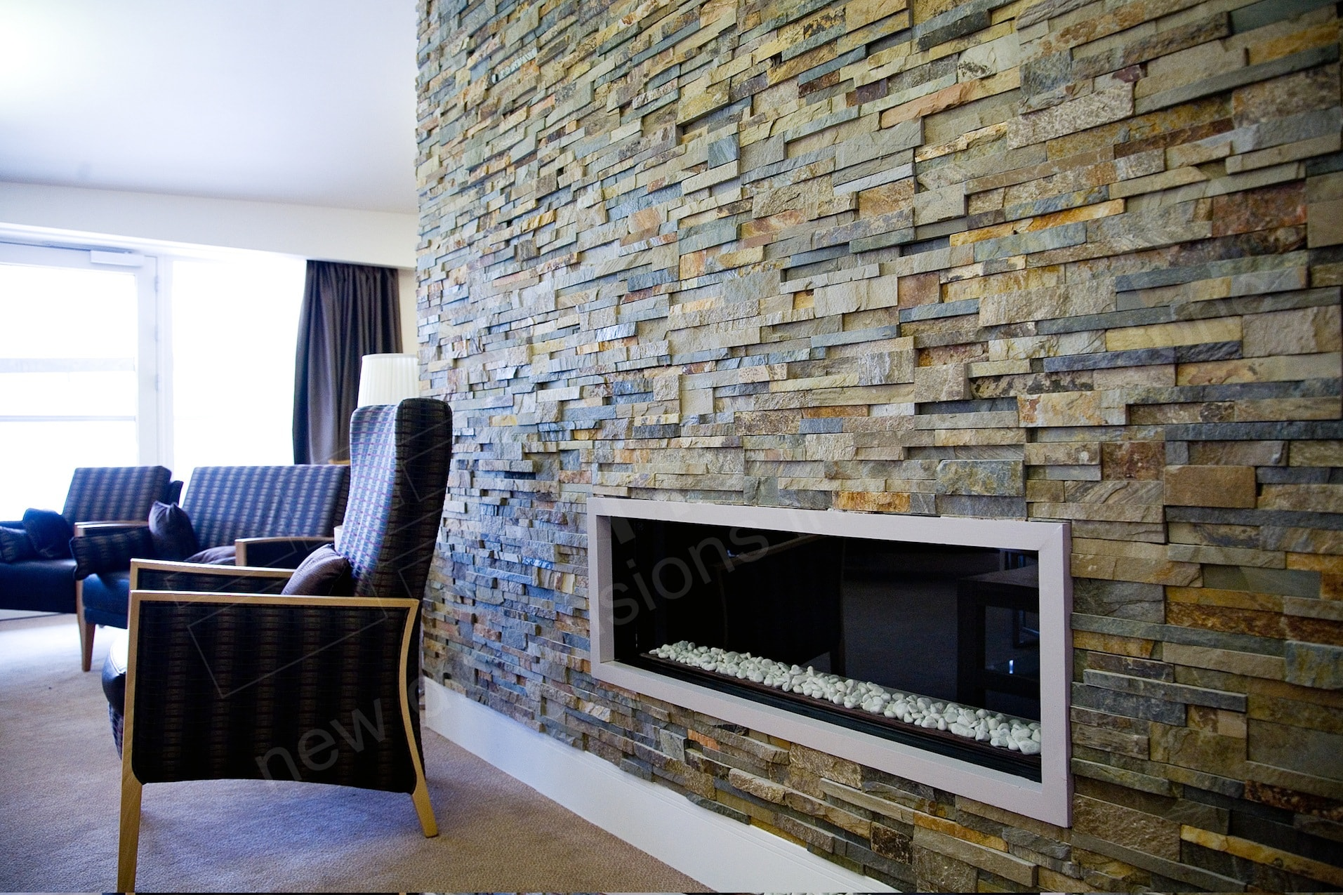 Norstone Ochre Blend Rock Panels used on a floor to ceiling fireplace with long linear gas fireplace insert
