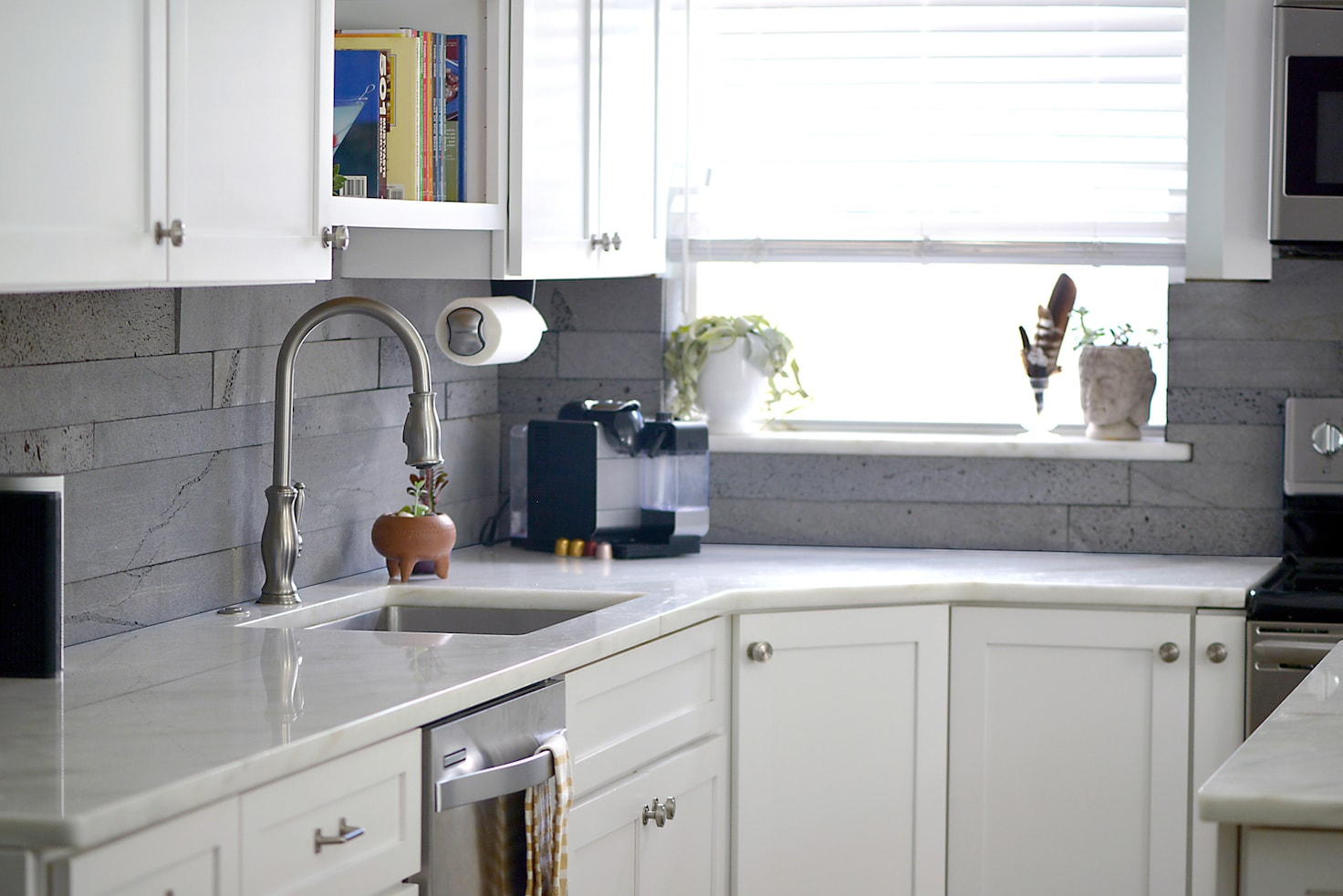 Planc Platinum used on a backsplash of a small modern kitchen with cabinets and white marble counter tops