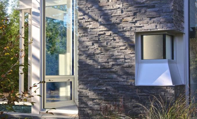 Norstone Charcoal Rock Panels used as stone siding on a residential exterior in the Hamptons