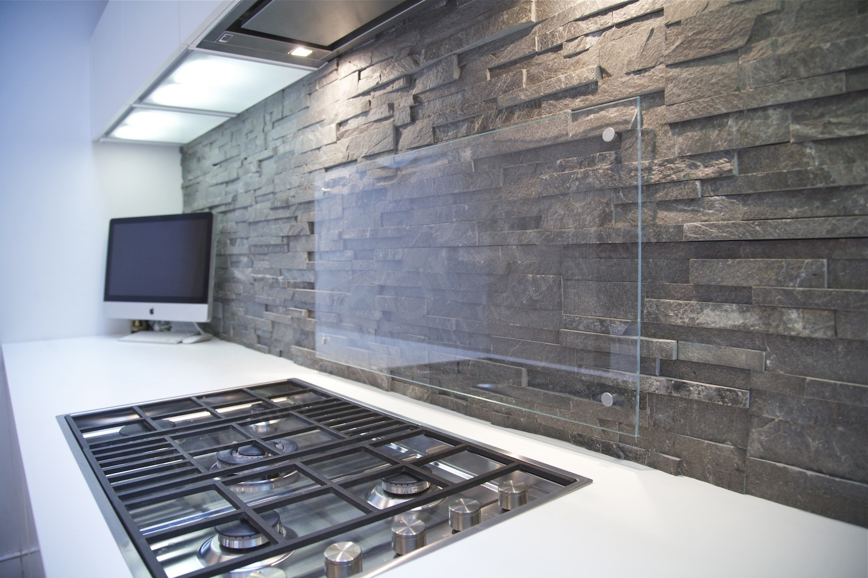 Norstone Stacked Stone Charcoal Rock Panels on a modern backsplash with a glass splatter guard