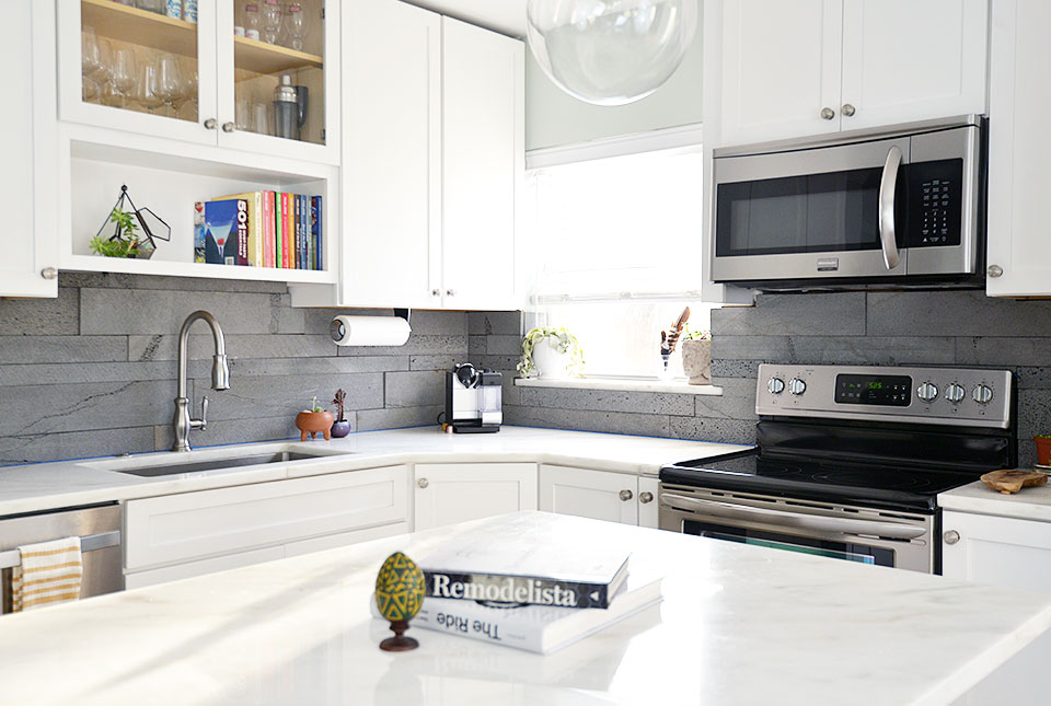 Norstone Planc tiles in platinum on a dodern kitchen with white countertops, white cabinets, and a small island