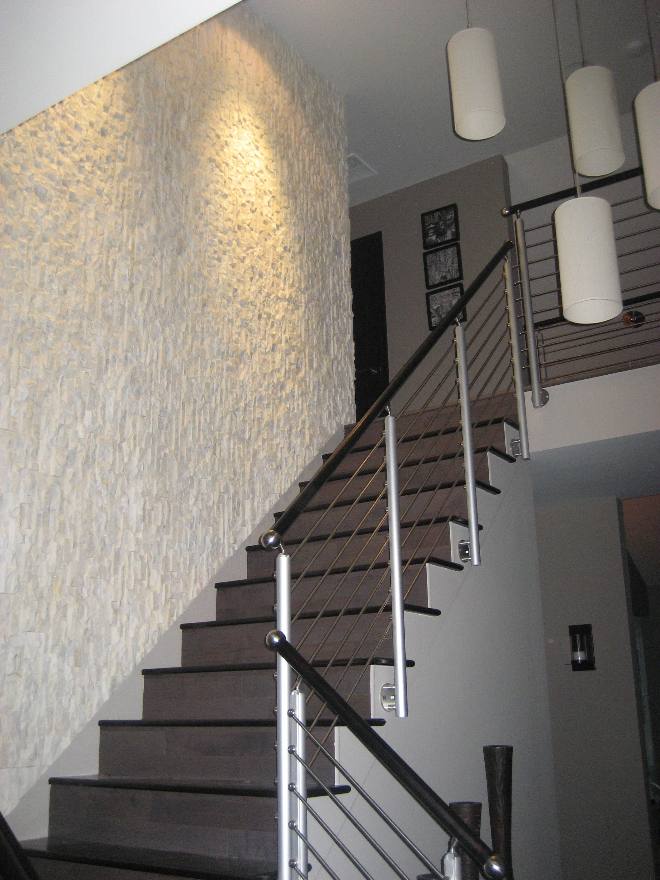 Norstone Stacked Stone White Rock Panels run vertically on stair case